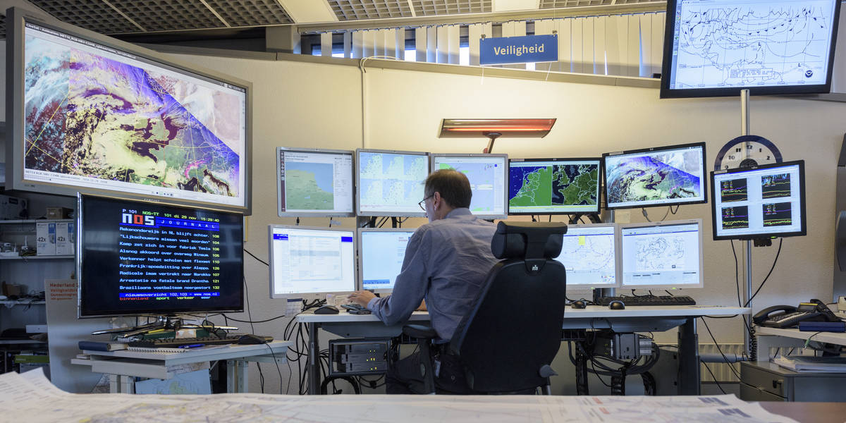 KNMI-meteorologen kijken in de weerkamer naar weermodellen en data op beeldschermen