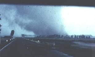 De windhoos enkele seconden voordat bij het verkeersplein een loods verwoest wordt en vervolgens een aantal auto's op het middenterrein zal worden geworpen. Let op het effect van de wind op de boomgroepen.
