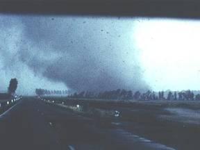 De windhoos enkele seconden voordat bij het verkeersplein een loods verwoest wordt en vervolgens een aantal auto's op het middenterrein zal worden geworpen. Let op het effect van de wind op de boomgroepen. (Foto: A.C. Frenks, R.M. Blewanus, H.L. v.d.Mer)