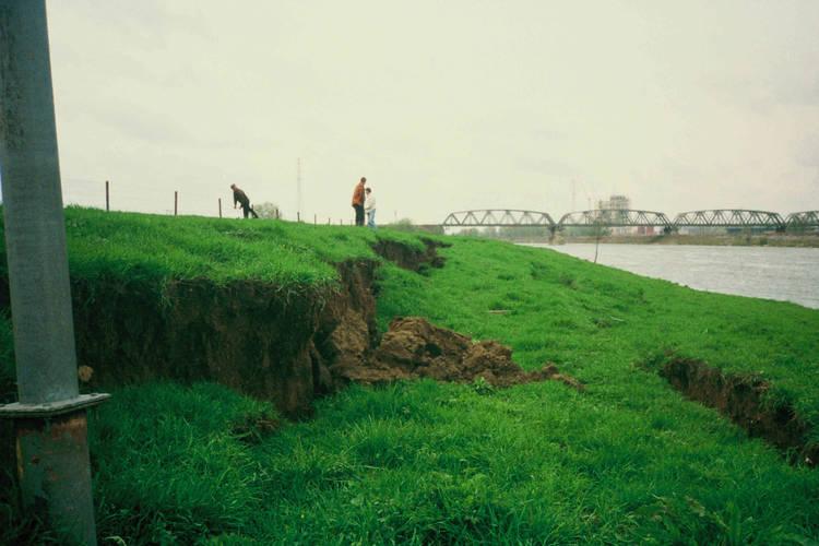 Waterkeringschade door aardbeving bij Roermond in 1992. Je ziet scheuren in de rechteroever van de Maas bij Leeuwen, tegenover Buggenum.
