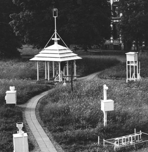 Oude temperatuurmeting in De Bilt. In de nok van de Pagode, de grote open hut met een puntdak, staat een thermograaf voor registratie van de temperatuur. Naast de Pagode staat een Stevensonhut, die op vrijwel alle weerstations werd gebruikt.