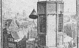 """foto van de toren van het gebouw Neptunus aan de Nieuwe Zijds Voorburgwal in Amsterdam, waarop """"geregeld bij dag en nacht seinen worden geheschen, die de verwachting betreffende storm aangeven"""". De foto is gemaakt tijdens """"het hijschen van een signaal"""""""