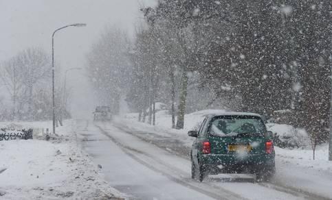 Auto's die rijden in de sneeuw.