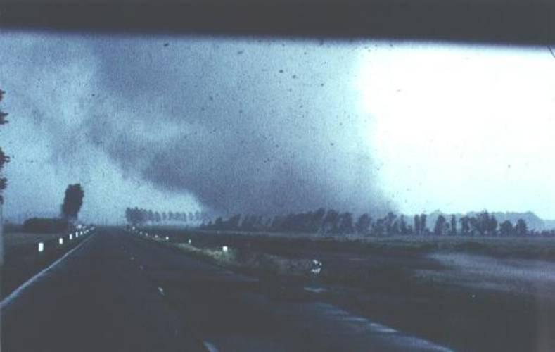 Windhoos van 25 juni 1967 enkele seconden voordat bij het verkeersplein een loods verwoest wordt en vervolgens een aantal auto's op het middenterrein wordt geworpen. Let op het effect van de wind op de boomgroepen