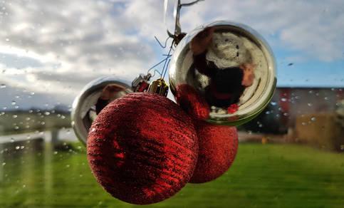 Kerstballen voor een beregend raam