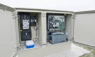 Boorgatstation; in rechtse deel de gps-antenne (wit bolletje) voor de satelliettijd, datarecorder, router voor dsl-verbinding en een accu (grijze kast). Linkerdeel van kast is van energiemaatschappij. Versnellingsmeter staat onderaan (dicht gedeelte)