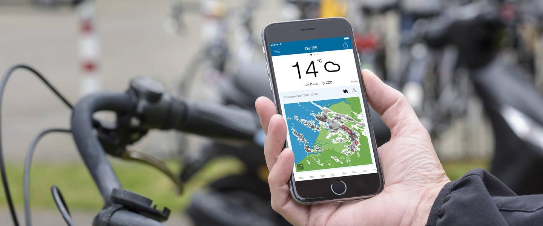 fietser toont knmi weer app op smartphone