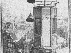 """De toren van het gebouw Neptunus aan de Nieuwe Zijds Voorburgwal in Amsterdam, waarop """"geregeld bij dag en nacht seinen worden geheschen, die de verwachting betreffende storm aangeven"""". De foto is gemaakt tijdens """"het hijschen van een signaal"""""""