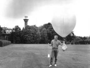 Oplating van een radiosonde in De Bilt door Kees Smith van het KNMI. Rechts op de foto zien we de ballon met de parachute waarmee de sonde (het kastje links) uiteindelijk omlaag komt ©KNMI