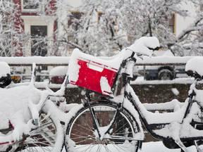Fiets met rode fietstas in de witte sneeuw