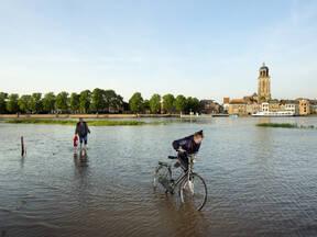 fietser loopt door hoogwater in deventer
