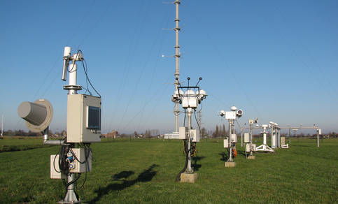 The BSRN station in Cabauw with in the background the 213 m tower. Central is the sun tracker with shadowed pyranometers (for diffuse irradiance), a pyrgeometer (downward longwave irradiance) and pyrheliometers (direct irradiance). Photo: Wouter Knap.