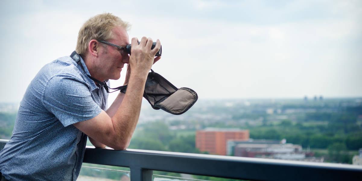 Hans van Gasteren kijkt door verrekijker naar aanwezigheid vogels vanuit uitkijktoren bij het bureau Natuur van de Koninklijke Luchtmacht