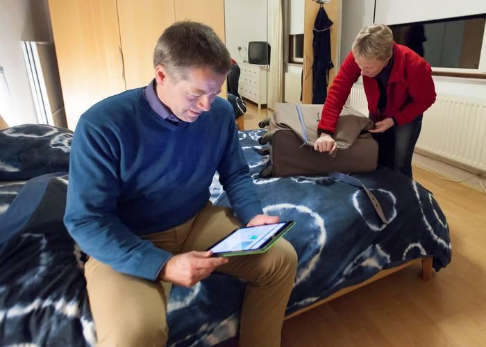 Carleen doet koffer dicht en Sander zit over zijn tablet gebogen