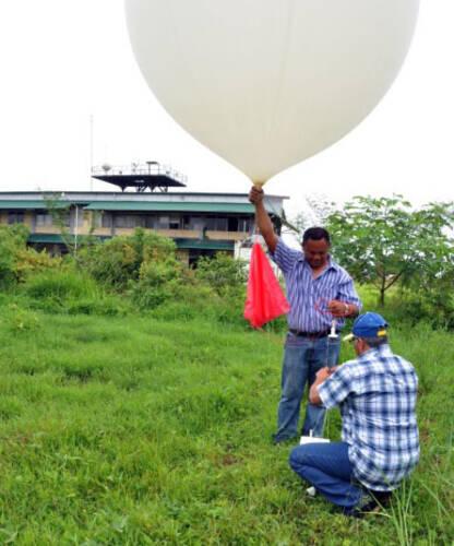 twee mensen laten een weerballon op in paramaribo