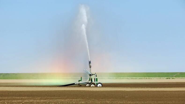 Op de foto is te zien hoe er water gesproeid wordt over droge landbouwgrond