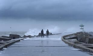 Twee mensen tijdens een storm op een pier