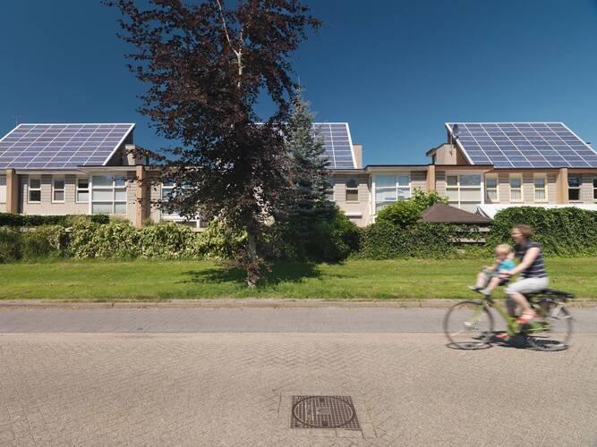 Zonnepanelen op daken van huizen in amersfoort en een vrouw met kind op fiets fietst over de straat
