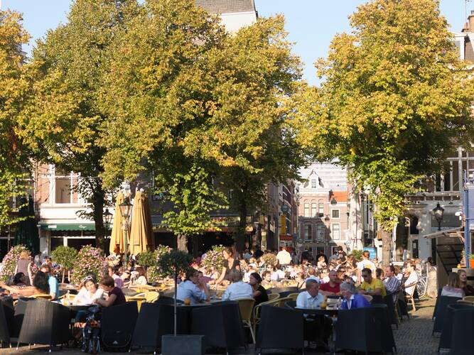 Mensen zitten op een terras in de zon