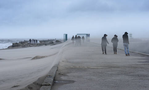 mensen aan de kust tijdens storm