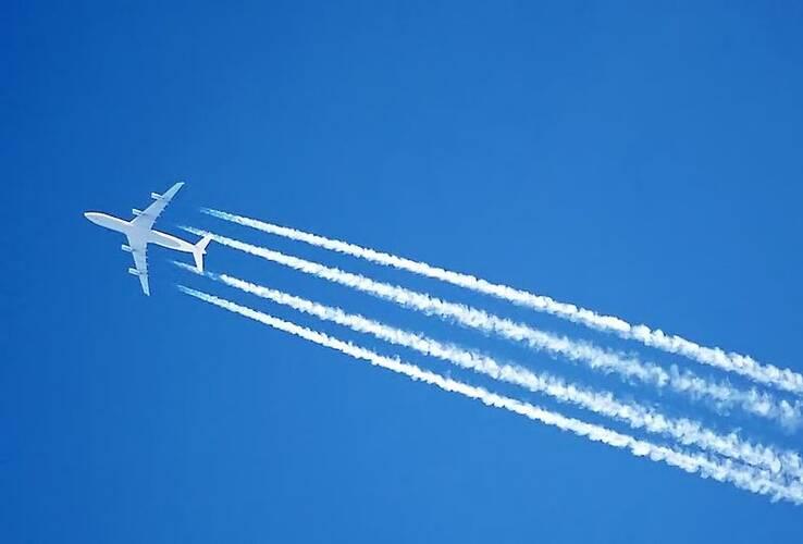 vliegtuig met viegtuigstrepen in blauwe lucht