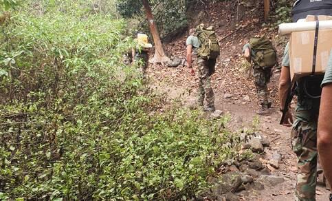 Mariniers vervoeren het materiaal voor het station te voet
