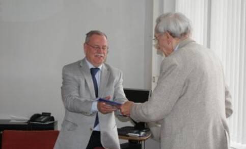 Wouter Nieuwenhuizen (plv hoofddirecteur KNMI) ontvangt het eerste exemplaar van Weermannen in Oorlogstijd uit handen van Tjitse Langerveld (foto: Titia Langerveld)