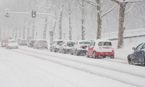 auto's wachten voor een stoplicht in de sneeuw