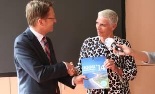 Staatssecretaris Wilma Mansveld neemt het rapport met de KNMI'14-klimaatscenario's in ontvangst uit handen van KNMI-hoofddirecteur Gerard van der Steenhoven (foto: Patricia van der Kooij, KNMI)