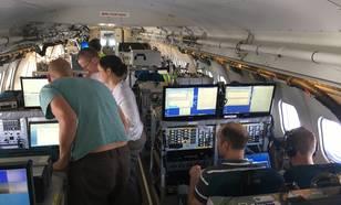Binnenin de BA-146, en zijn bemanning. Tijdens de vlucht wordt er continu gemeten, en gejaagd op de beste omstandigheden, in dit geval rook in combinatie met wolken